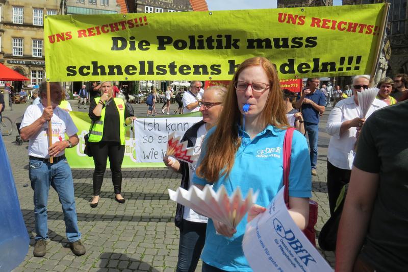 Pflegeaktivisten halten ein Protest-Banner hoch mit der Aufschrift: