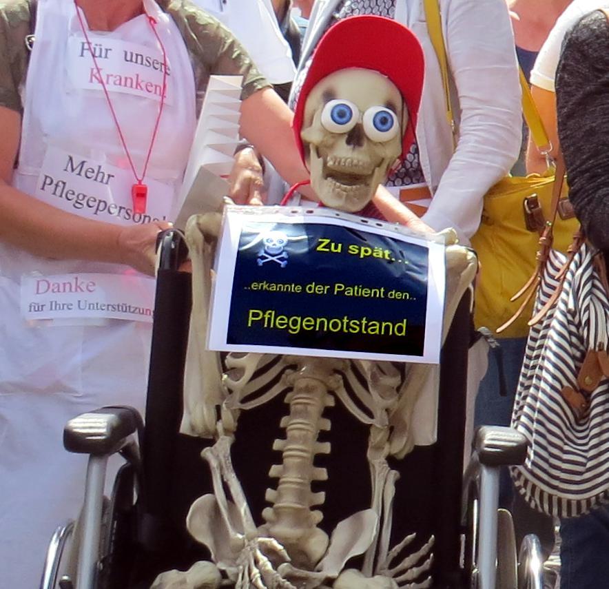 Skelett im Rollstuhl mit Schild um den Hals
