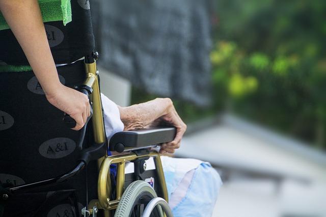 Frau fährt eine Person im Rollstuhl